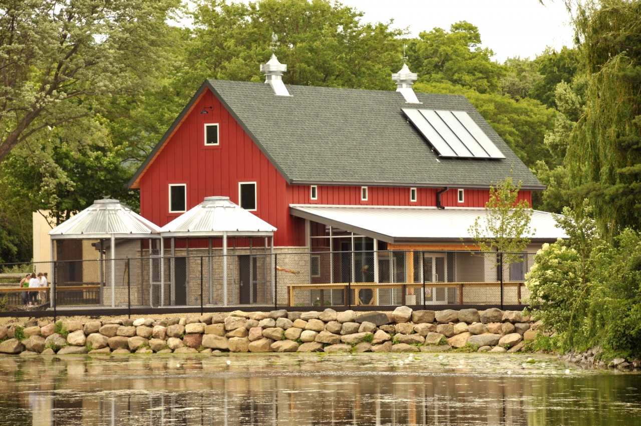 red sided timber frame barn built with solar power and round aluminum aviaries